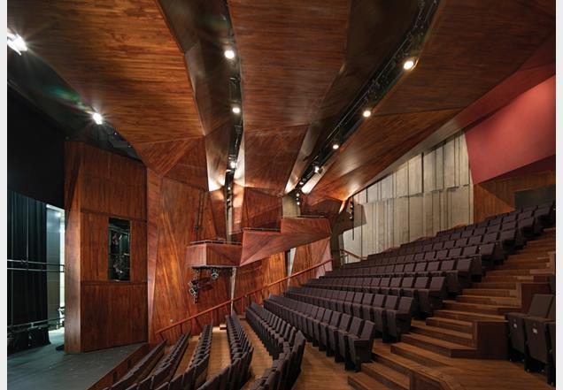 The main auditorium is conceived as a faceted timber grotto, spanned by three lighting arches.